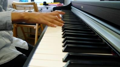 Gros plan sur les mains d'une élève de piano